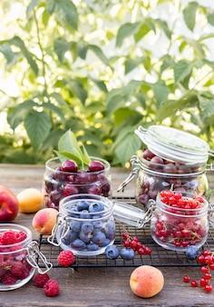 Ассортимент свежих сезонных ягод в стеклянных банках на размытом фоне сада