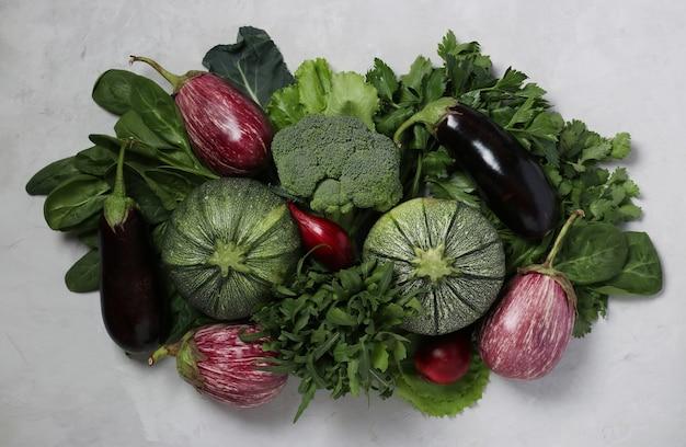 밝은 회색 배경에 호박, 가지, 양파, 브로콜리, 아루굴라, 시금치, 실란트로와 같은 신선한 야채와 허브의 구색. 채식주의 자 음식. 위에서 보기