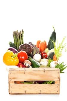 白い背景の上の木枠に新鮮な野菜の品揃え