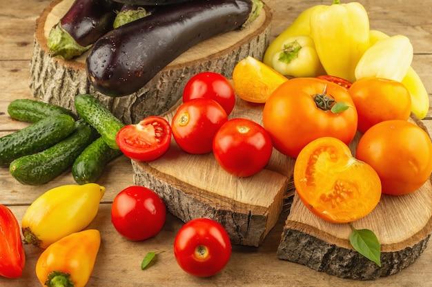 木製の背景に新鮮な野菜の品揃え。完熟トマト、ナス、きゅうり、ピーマン、クローズアップ