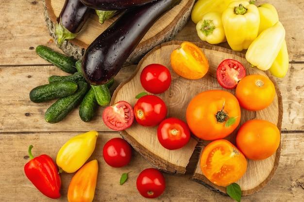 木製の背景に新鮮な野菜の品揃え。完熟トマト、ナス、きゅうり、ピーマン、上面図
