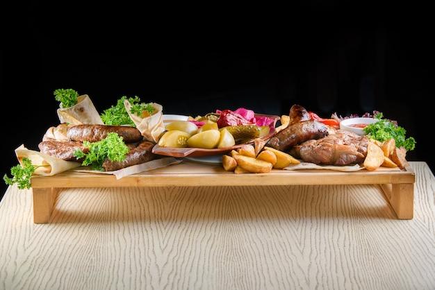 테이블의 나무 쟁반에 튀긴 고기, 감자, 소시지, 피클, 토마토, 고추, 허브, lavash의 구색.