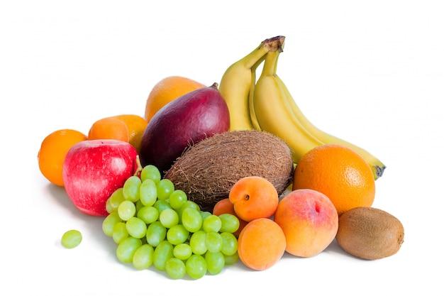 Ассортимент фруктов бананы, манго, зеленый виноград, яблоко, кокос, персики, абрикосы, мандарины и киви являются изолированными.