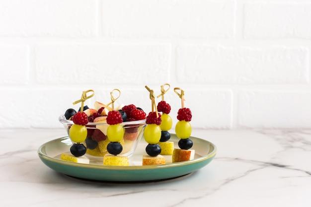 Ассортимент фруктовых канапе на тарелке на фоне белой кирпичной стены. праздничная еда.
