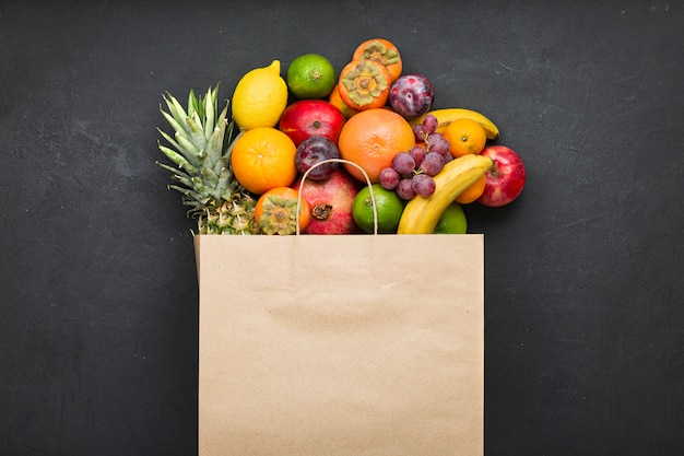 Ассортимент фруктов в бумажном пакете на черном бетоне. концепция витаминов в рационе человека.