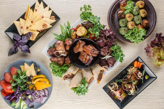 白い木製のテーブルに焼き肉、グルジア料理のスナック、チーズ、野菜のカットの品揃え。上面図。