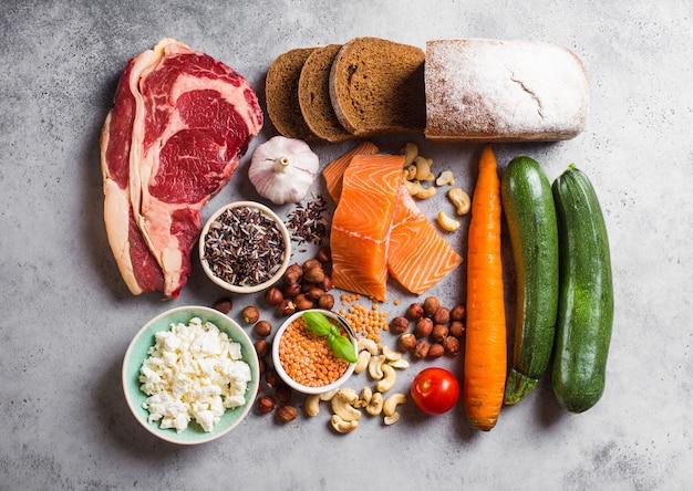 健康的なバランスの取れた食品組成の品揃え:肉、魚、野菜、パン、シリアル、豆、石の背景。健康的な食事を調理するための原材料、ダイエットに適した、きれいな食事のコンセプト