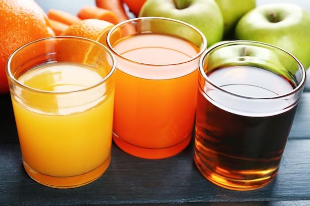 木製のテーブルの上の健康的なフレッシュジュースとフルーツの品揃え