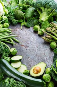 Ассортимент здоровых органических зеленых овощей для сбалансированного питания. веганский, вегетарианский, цельный, растительный, концепция экологически чистого питания. скопируйте космический фон
