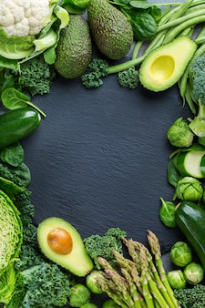 Ассортимент здоровых органических зеленых овощей для сбалансированного питания. веганский, вегетарианский, цельный, растительный, концепция экологически чистого питания. вид сверху плоская копия космического фона