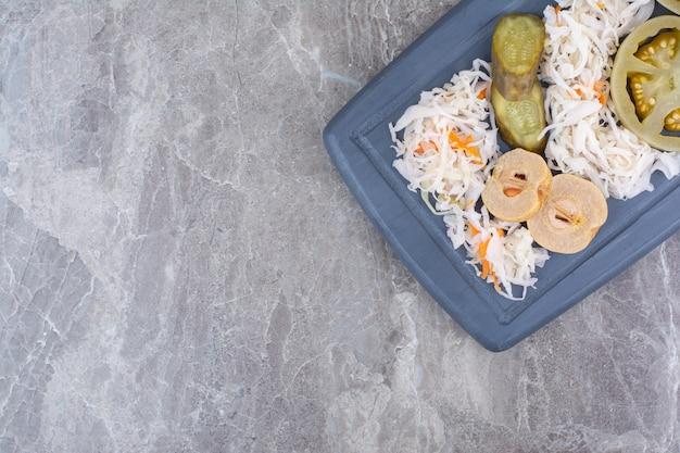 Ассортимент домашних солений на темной тарелке.