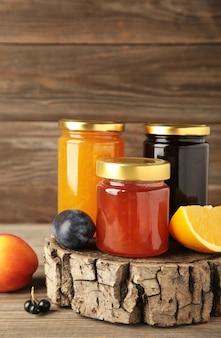 회색 배경에 다양한 잼, 신선한 제철 딸기, 과일. 세로 사진