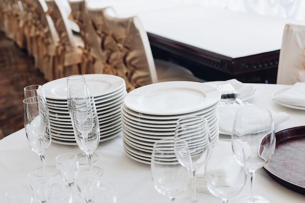 白いテーブルの上の台所用品の品揃え。白いプレートのスタック、空のシャンパンフルート、ボトル入り飲料水と氷のバケツが付いたグラスのある白い円卓をご覧ください。