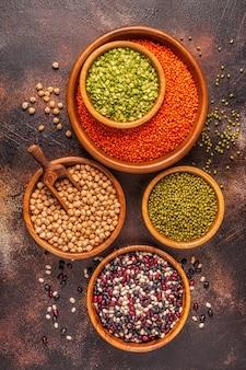 マメ科植物の品揃え-レンズ豆、エンドウ豆、緑豆、ひよこ豆、さまざまな豆。上面図。