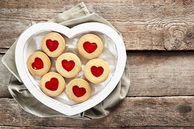 木製の背景、クローズアップの布とボックスの愛のクッキーの品揃え