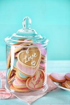 青い背景の上の瓶に愛のクッキーの品揃え