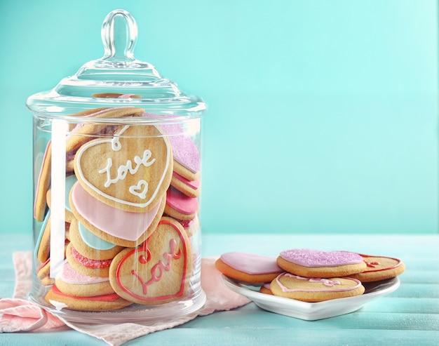 Ассортимент любовного печенья в банке на синей поверхности