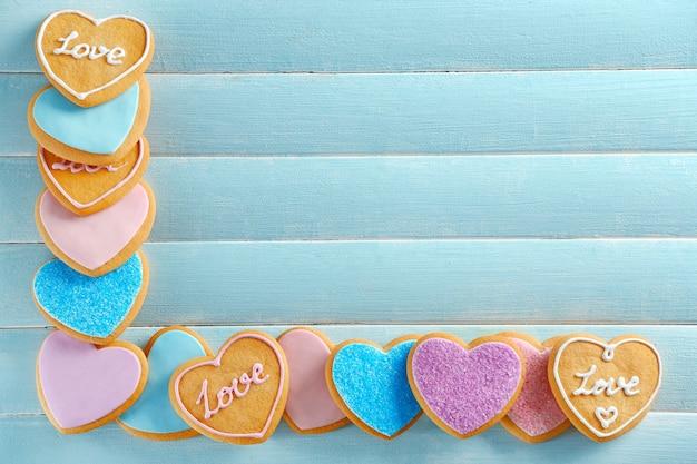 Ассортимент любовного печенья на синем фоне деревянного стола, копией пространства
