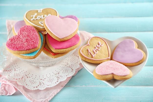 青い木製のテーブルの背景に愛のクッキーの品揃え
