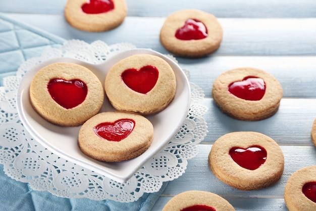 푸른 나무 테이블 표면에 다양한 사랑 쿠키