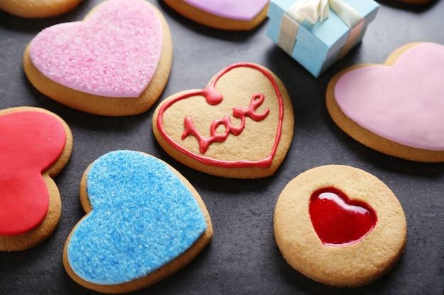青い木製のテーブルにギフトと愛のクッキーの品揃え
