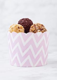 분홍색 종이 파티 컨테이너에 고급스러운 화이트 초콜릿 다크 초콜릿 사탕의 구색
