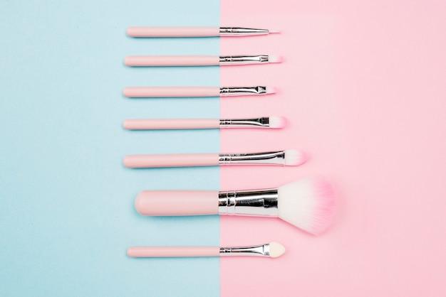 Ассортимент кисточек для макияжа на двухцветном фоне