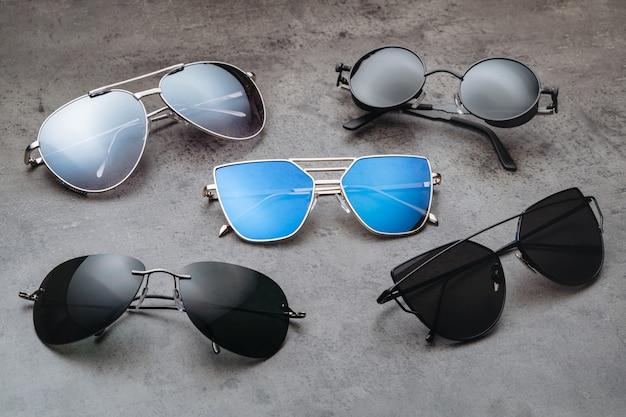 Ассортимент новых модных современных солнцезащитных очков хипстера на столе в оптическом магазине