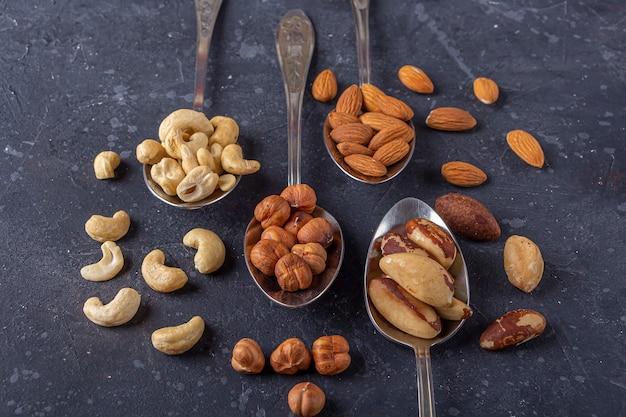 Ассортимент орехов кешью, фундука, миндаля, бразильских орехов на металлических серебряных ложках. здоровые вегетарианские закуски.
