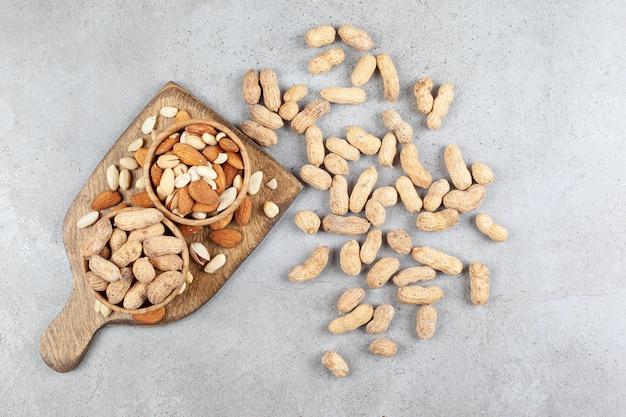 Ассортимент орехов в мисках на деревянной доске и разбросанных по мраморной поверхности.