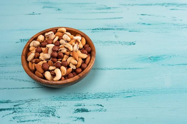 青い木製のテーブルの上の木製のボウルにナッツの品揃え。カシューナッツ、ヘーゼルナッツ、アーモンド。