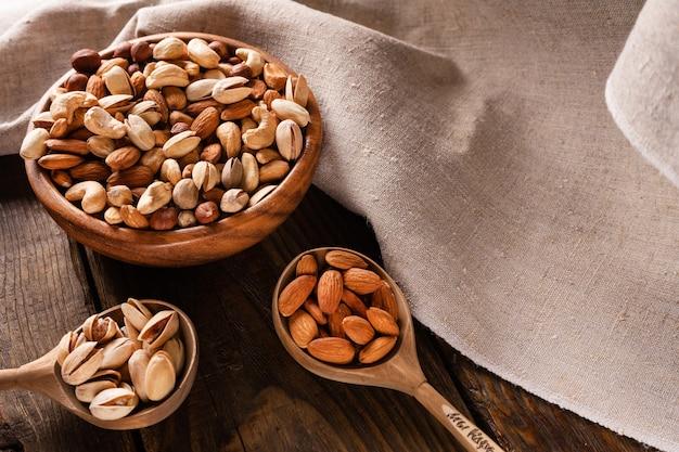 暗い木製のテーブルの上の木製のボウルにナッツの品揃え。カシューナッツ、ヘーゼルナッツ、アーモンド、ピスタチオ。