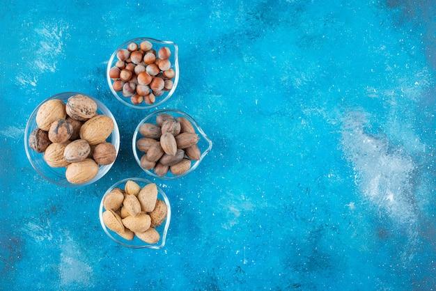 青いテーブルの上に、ボウルにナッツの品揃え。