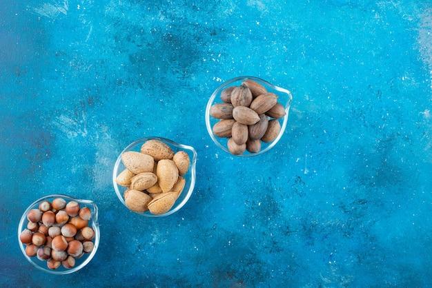 파란색 테이블에 그릇에 견과류의 구색.