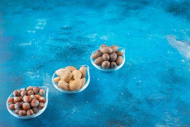 Ассортимент орехов на мисках, на синем столе.