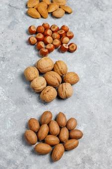 Ассортимент орехов на бетонной поверхности. фундук, грецкие орехи, орехи пекан, арахис, миндаль, вид сверху