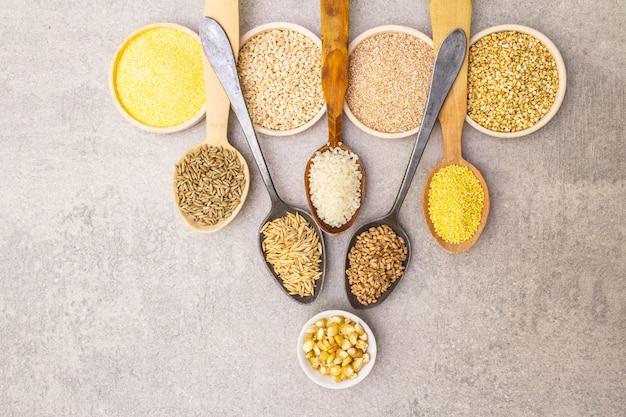 Ассортимент органических круп, бобовых и цельных зерен в мисках и ложках