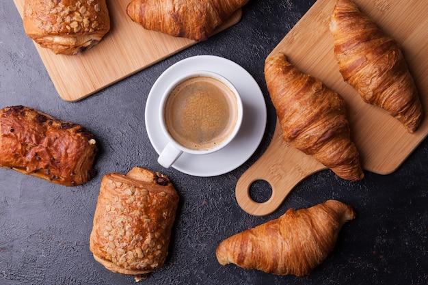 나무 테이블 배경에 커피 컵과 패스트리의 구색. 프랑스 요리.