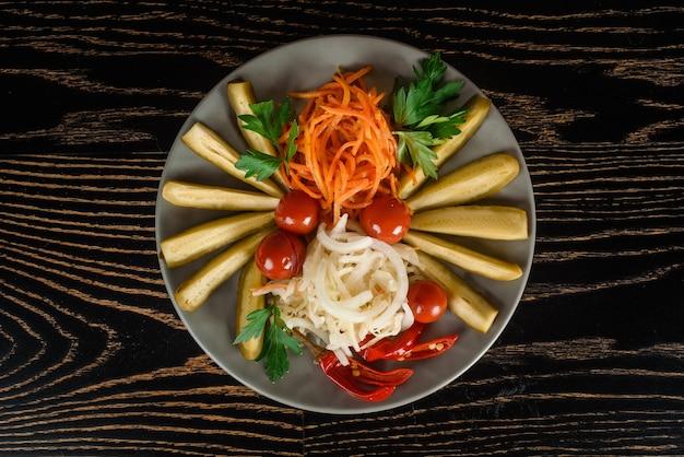 Ассортимент солений, помидоров черри, чили с морковью, луком и петрушкой на серой тарелке на темном деревянном столе. вид сверху.