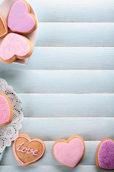 푸른 나무 테이블 표면에 있는 분홍색 사랑 쿠키의 구색, 복사 공간