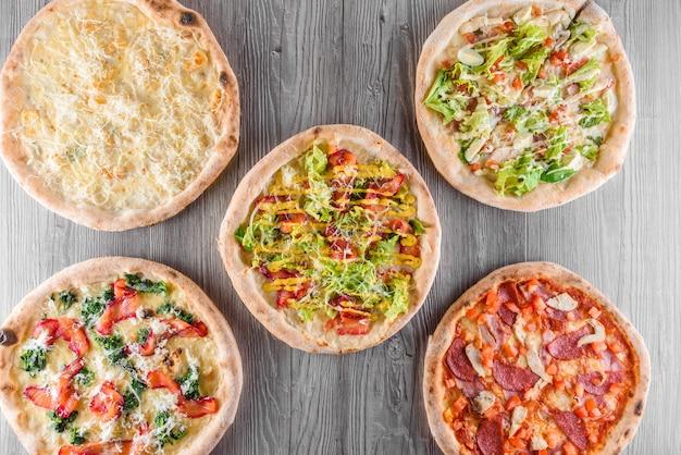 고기, 살라미 소시지, 프로슈토, 토마토, 도르 블루 치즈, 모짜렐라, 파마산, 샐러드, 시금치, 나무 판에 붉은 생선을 곁들인 피자 구색. 4 치즈 피자, 시저, 평면도.