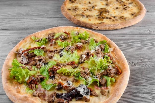 肉、生ハム、トマト、モッツァレラチーズ、パルメザンチーズ、サラダ、マッシュルーム、木の板にクリームソースを添えたピザの品揃え。