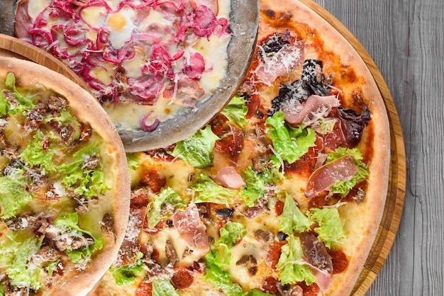 肉、サラミ、生ハム、トマト、モッツァレラチーズ、パルメザンチーズ、サラダ、青玉ねぎ、ウズラの卵を木の板に載せたピザの品揃え。上面図。