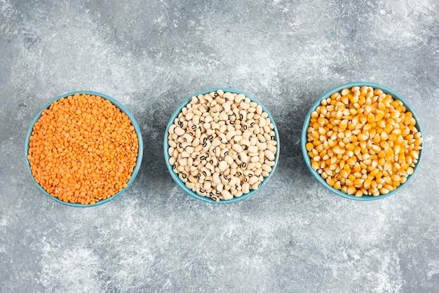大理石のテーブルに生豆、とうもろこし、赤レンズ豆の詰め合わせ。