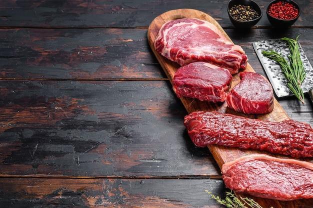 Ассортимент сырых стейков из говядины филе вырезки миньон, рибай, стриплойн или нью-йорк, юбка, мачете