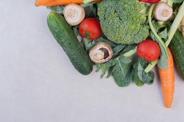 Ассортимент сырых овощей на белой поверхности.