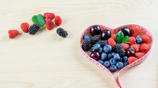 健康的な食事とフルーツダイエットのシンボルとしてテープを投薬、木製のテーブルに熟した新鮮な果物の品揃え。