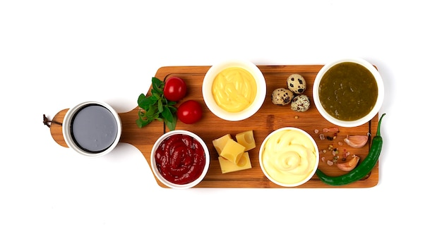 Ассортимент соусов кетчуп, майонез, сыр, соевый, зеленый, на разделочной доске, с ингредиентами, на деревянном фоне, вид сверху, без людей. фото высокого качества