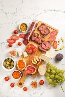 白い石の背景にソーセージとチーズ、サラミカマンベールブリー、ブドウ、バゲットスライス、オリーブの品揃え。前菜の前菜と前菜の軽食。白い大理石の背景。上面図