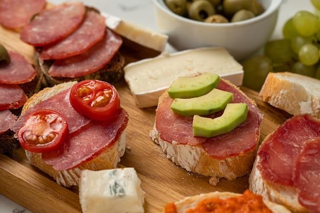 白い石の背景にソーセージとチーズ、サラミカマンベールブリースライス、オリーブの品揃え。前菜の前菜と前菜の軽食。白い大理石の背景。閉じる